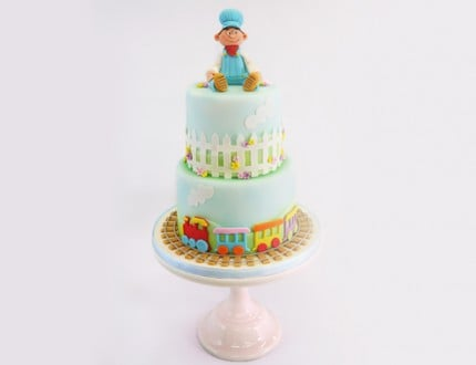 little boy model on top of two tier cake